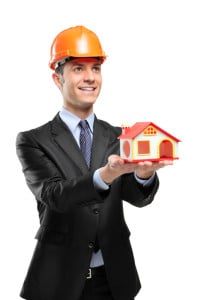 a smiling foreman holding a model house